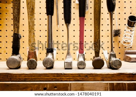 Row of hammers standing on their heads in a line; various shapes and sizes of hammer tools together in a line #1478040191