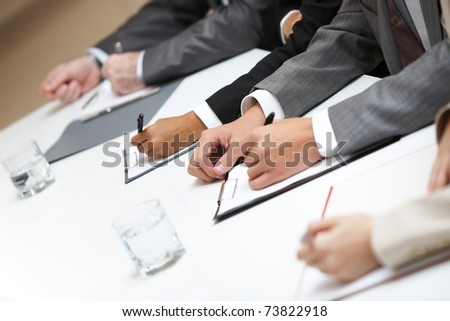 Row of hands making notes