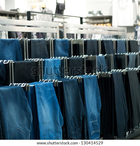 Row of hanged jeans in a shop
