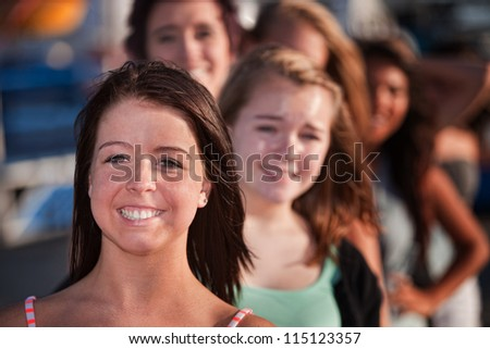 Row of happy smiling female teenagers outdoors
