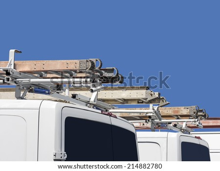 Row of home repair contractor vans and ladders Rear view of white utility truck with metal ladder on vehicle roof Blue sky background