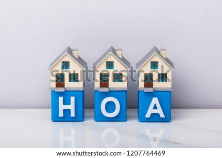 Row Of House Models On Blue HOA Cubic Blocks Over Reflective Desk #1207764469