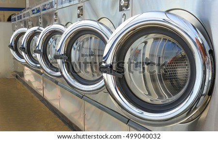 Row of industrial laundry machines in laundromat. #499040032