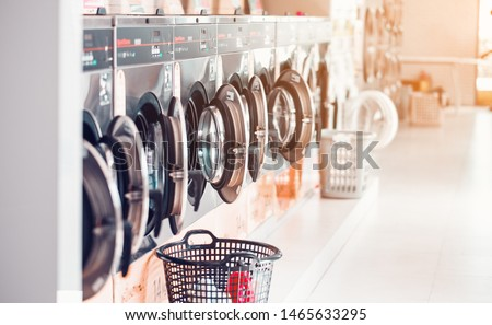 Row of industrial laundry machines in laundromat  in a public laundromat, with laundry in a basket , Thailand