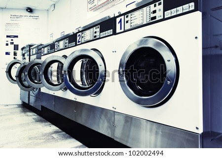 row of industrial washing machines in a public laundromat