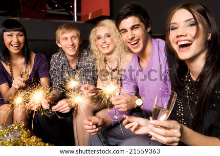 Row of joyful friends with champagne and xmas lights celebrating New Year