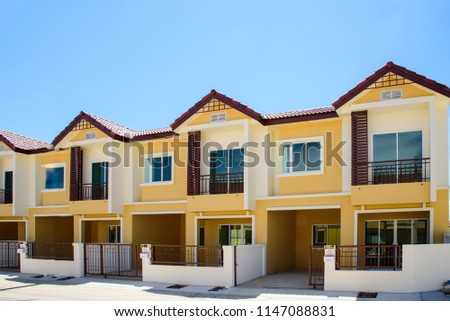Row of just finished new yellow townhouses.