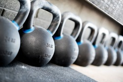 Row of kettlebell or girya weights in a gym with selective focus to a 24 kg weight in a fitness and active healthy lifestyle concept