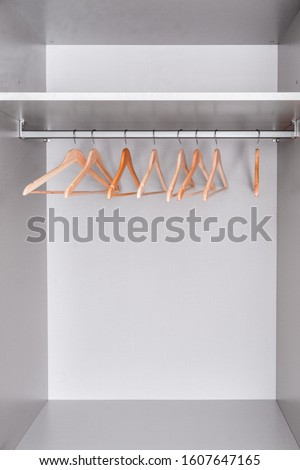 row of lacquered wooden light hangers for clothes hangs in wardrobe on metal rod. There's empty shelf on top. Accessories made of environmental material.