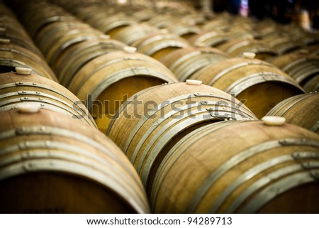 Row of Large French Oak Red Wine Barrels in a Wine Warehouse - stock photo