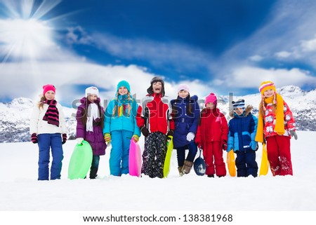 Row of large group of kids, friends, boys and girls standing together outside in snow