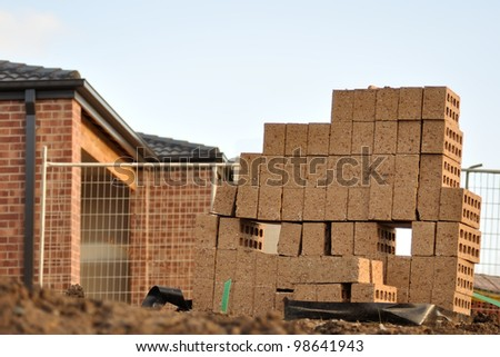 Row of leftover bricks at new house construction site, new house blurred in background