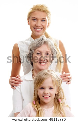 Row of little girl, grandmother, mother looking at camera in line