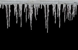 Row of long icicles on black background