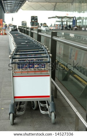 Row of luggage carts with a blank billboard in airport area