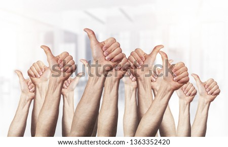 Row of man hands showing thumb up gesture. Agreement and approval group of signs. Human hands gesturing on light blurred background. Many arms raised together and present popular gesture.
