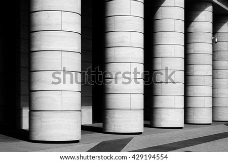 Row of marble columns with dark gaps and pavement floor. Black and white photo. Architectural details with rhythm