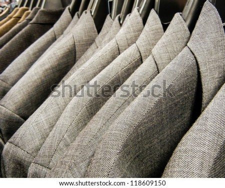 Row of men's suit jackets hanging in a supermarket department store.