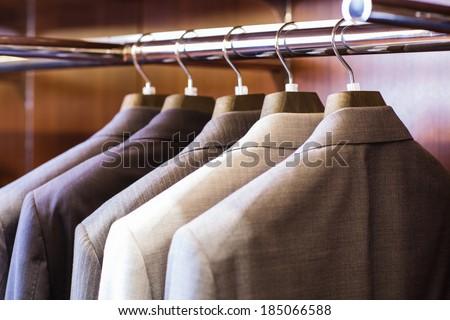 Row of men\'s suit jackets hanging in closet