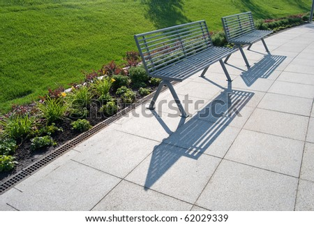 Row Of Metal Park Benches With Green Grass Behind Stock Photo ...