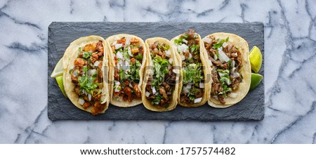 row of mexican street tacos on slate with carne asada and al pastor in corn tortilla Stok fotoğraf ©