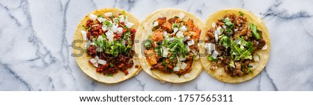 row of mexican street tacos with carne asada and al pastor in corn tortilla wide banner composition Stok fotoğraf ©