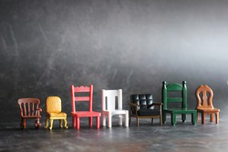 Row of miniature chairs in various style in vintage tone background. Doll furniture house on the black floor.