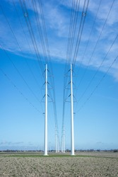 Row of modern high-voltage pylons with power lines for transporting electricity in the Dutch landscape