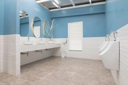 Row of modern white ceramic washbasins in a public blue-and-white bathroom or restaurant or hotel or shopping mall interior design.