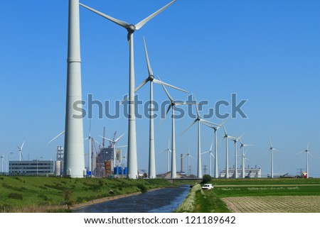 Row of modern wind turbines and a power plant being constructed in the Eemshaven, Holland. - stock photo