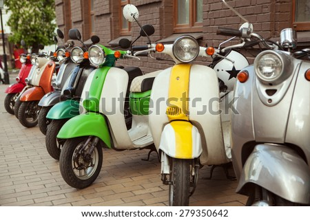 row of mopeds on a street