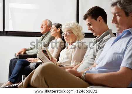 Row of multiethnic people waiting for the doctor in hospital lobby