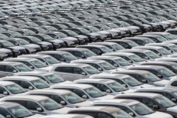 Row of new cars for sale in port. New automobiles background