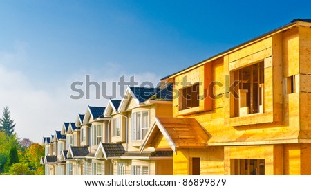 Row of new houses with one still under construction