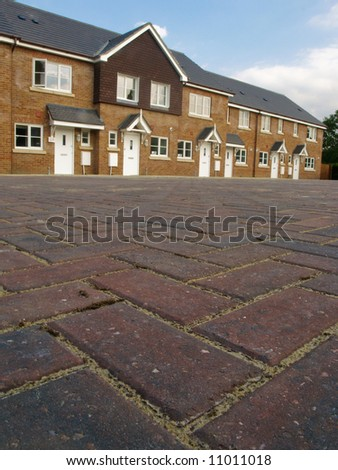 Row of new red brick terraced houses with cobbled pavior street in foreground, UK.
