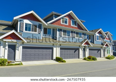 Row of new residential townhouses on a street on sunny day. Family townhouses with concrete driveways and asphalt road in front. British Columbia, Canada.