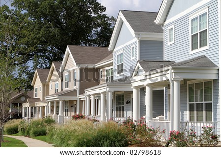 Row of newly constructed townhomes in a sidewalk neighborhood.
