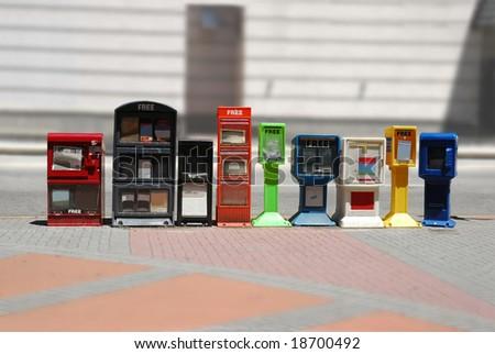 Row of news stands (newspaper dispensers) beside a street by a sidewalk