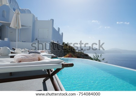 row of of beach chairs at a luxury resort swimming pool Canaves oia Santorini Greece September 2017 #754084000