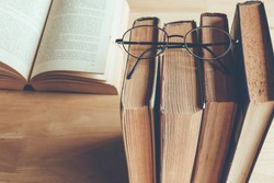 Row of old books with reading glasses above , vintage color tone
