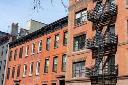 Row of Old Brick Residential Buildings in Hell's Kitchen of New York City with Fire Escapes
