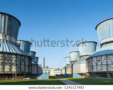 Row of old fan cooling towers for cooling circulating water of chemical plant under clear blue sky. #1245117481