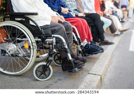 Row of old people in wheel chairs on the sidewalk. Selective focus