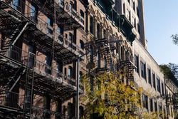Row of Old Residential Buildings with Fire Escapes in Nolita of New York City during Autumn