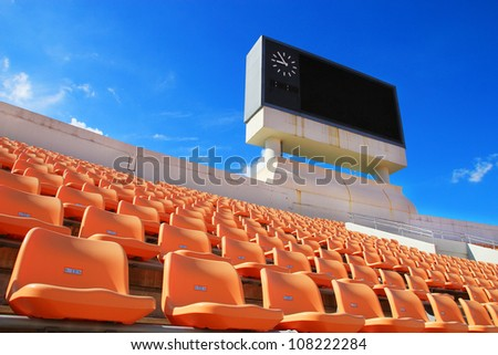 row of orange seats and score board in stadium