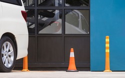 Row of orange traffic cone and plastic poles with white car park on parking lot area beside glass wall of modern restaurant