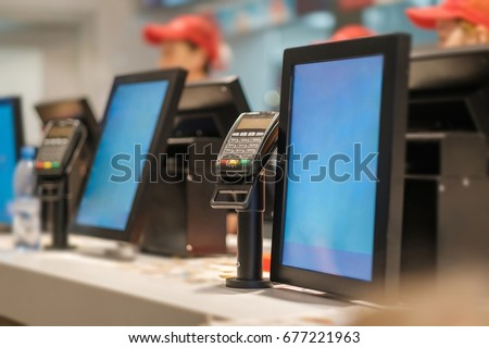 Row of order desks with computer screen and card payment terminal in fast food restaurant #677221963