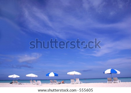 Row of parasols on white sand beach