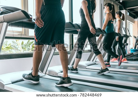 Row of people exercising on treadmills at the bright modern gym, indoor fitness sport healthy concept.