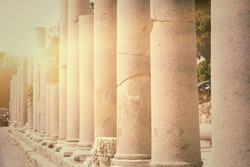 Row of pillars backlit in town Side (Turkey), ancient Roman architecture, ruins of aged castle, religious building in bright sun light, vintage photo
